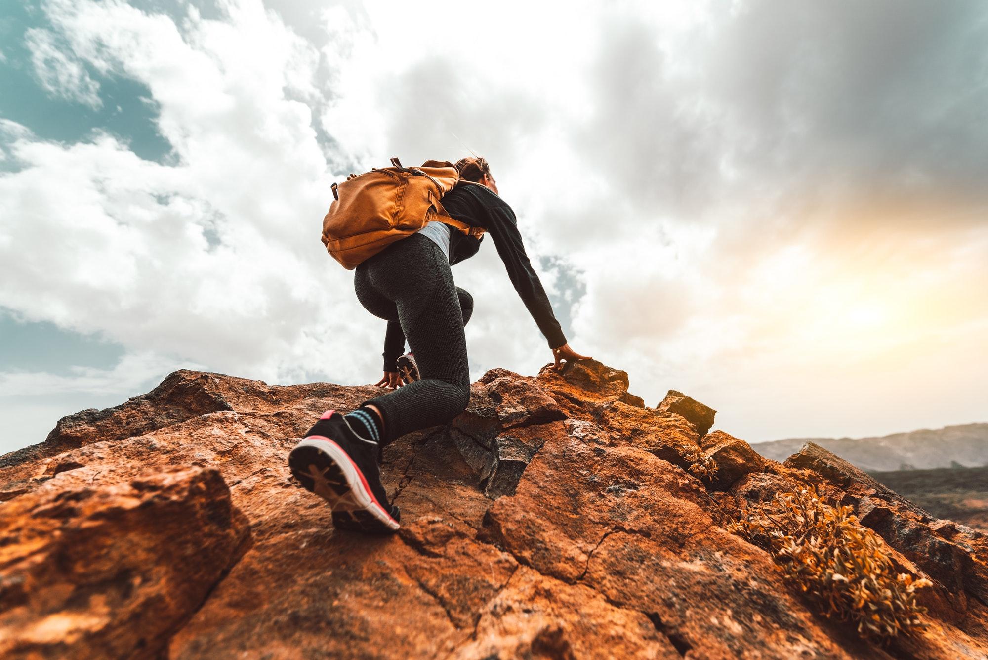 Success woman hiker hiking on sunrise mountain peak